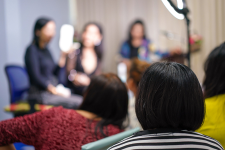audience and participant listen to teacher and lecturer at the front of stage about women face make up.