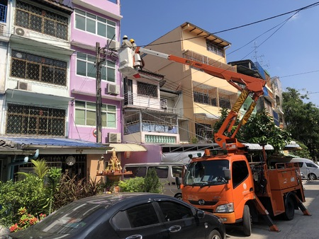 Pom Prap Sattru Phai District, Bangkok, Thailand - 19 March 2018: Electrician on the truck crane shifted up to check and repair main electric power line in Soi ManSri area, PomPrab, Bangkok, Thailand.
