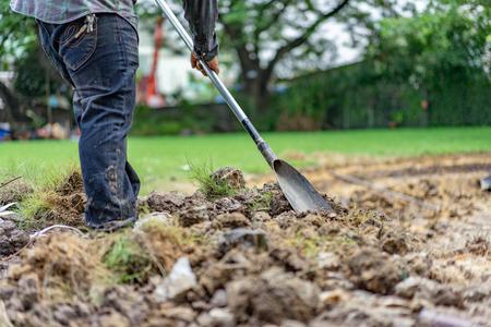 Le jardinier creuse le sol avec son équipement pour le jardinage et prépare la terre pour la plantation.