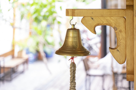 brass bell hand on to the wooden big plate stick on the pole wall. Standard-Bild