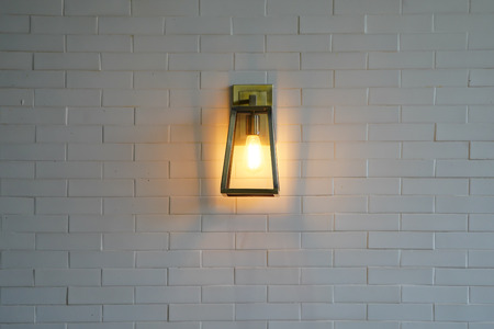 Square steel lamp tungsten/warm light on the white brick wall. Фото со стока