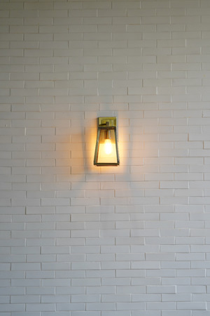 Square steel lamp tungsten/warm light on the white brick wall.