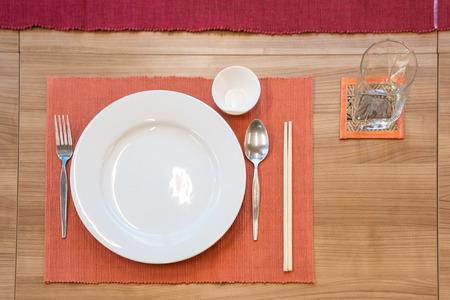 japanischer, moderner Esszimmerstil mit orientalischem Gericht, Gabel, Löffel, Serviette und Glas auf dem Tisch.