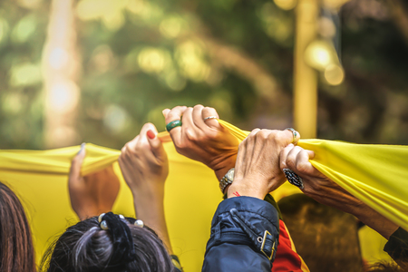 united people; close up their hands, rise up the holy huge yellow buddhism flag together in religion local traditional ceremony.