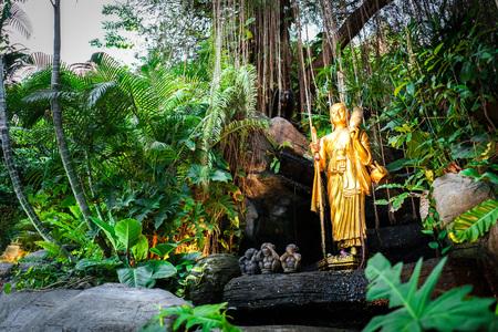 Goldener Anhänger Buddha-Statuen zu Fuß auf dem Felsen, der mit Pflanzen und Weinreben umgibt., Golden Mount, Bangkok, Thailand.