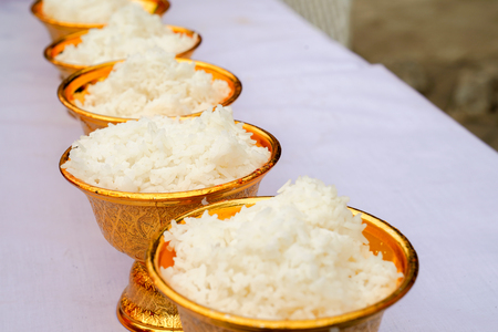 cooked Jasmine rice in the gold pan on the white table ready for Thai Buddhism traditional ceremony.