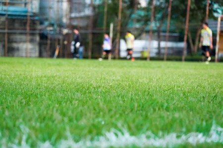 Grass in the football field with blur player play football background.