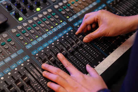 Dj controles sound controller and plays mixed edm music in the concert nightclub at a party. Stock Photo