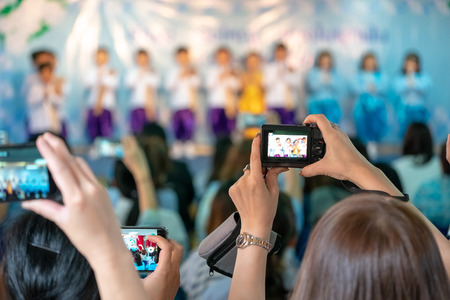 Asian parents recording vdo and photo shooting in their kids school event, Bangkok, Thailand.