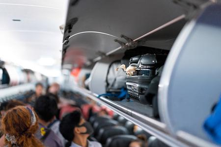 Equipaje en el asiento del pasajero superior de la estantería del avión