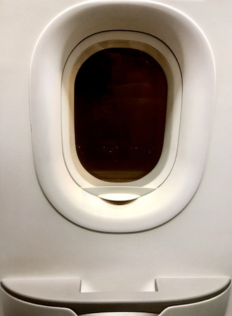 close up emergency window and door of low cost plane, photo shoot from the inside out at the night