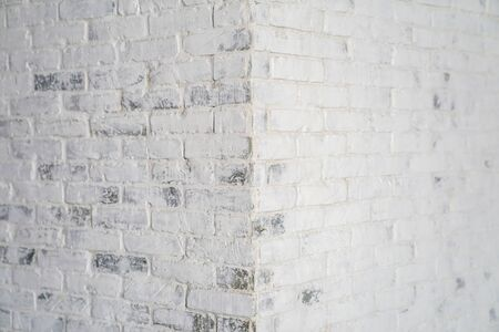 White old scratched brick at the corner in the afternoon.