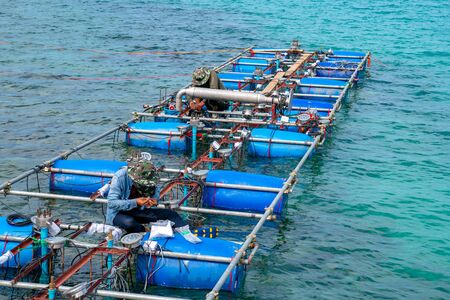 Workers settle and setup the waterworks fountain machine on the surface of the sea.