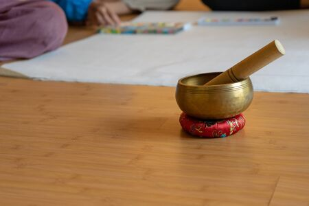 Brass bowl on the cloth base lay on the wood floor. Its the Asian vintage gimmick to ring a signal and sound for notice the seminar and workshop for attension to speaker. Stock Photo