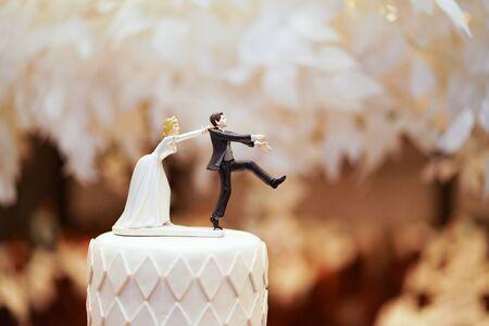 bruidegompop en standbeeld rennen weg, maar de bruid kan hem eindelijk vangen. de grappige pop met het huwelijksverhaal bovenop de taart. Stockfoto