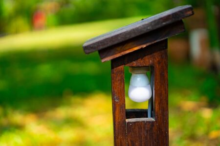 Vintage outside Wood lamp structure but inside is LED lamp settle in the garden.