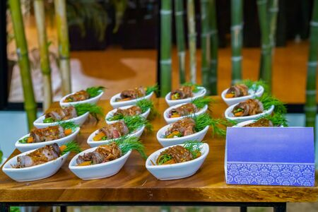 Griiled rolled beef and vegetable with spicy dipping souce. Cocktail food applied between modern style and local Thai food ready for serve in outdoor garden event. Stock Photo