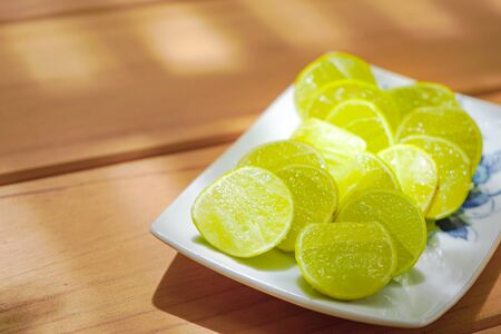 Lemons or Limes are slied for ingredient to cook and beverage. It's arranged on the rectangle white bowl square on wooden table plate in the garden with sun light.
