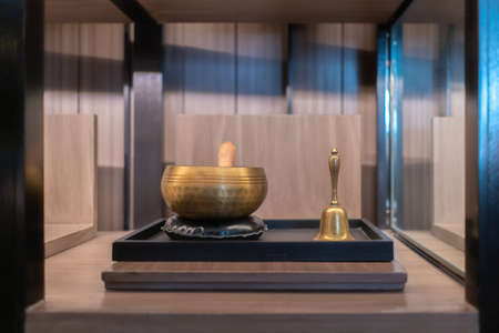Vingtage brass bowl and hand ring bell in the square wood shelf.