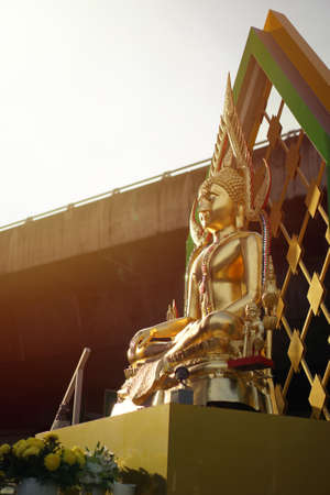 Portrait Gold Buddha statue with expressway behind and sunlight effect