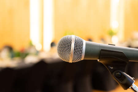 Close up to microphone beside the podium with blur long black table dinner time in tungsten warm light.