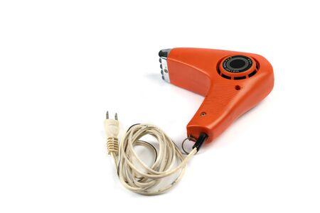 Vintage orange hair dryer on white background with rolled cable buttom. Foto de archivo