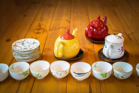 Yellow White and Red tea pot on the wood table with white dish and cup in the front row of them.