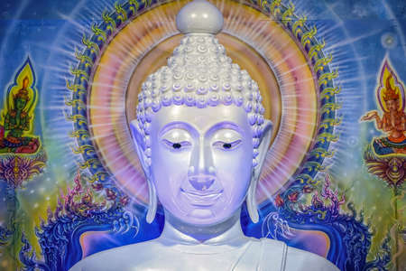 Great white Buddha statue with blue background wall.