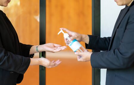 Two Asian business man and woman in black suit are washing their hands by alcohol gel before enter the meeting seminar room.
