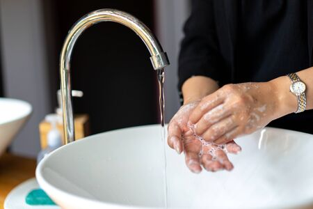 Business woman in dark black suit is washing her hand in sink.
