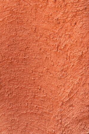 red - orange colour on the abstract random texture curve cement on the wall at afternoon time.