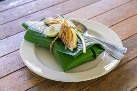 Wraped Thai food set cover by banana leaf ready to serve. Inside banana leaf is PadThai, The Traditional of Thailand Fried noodle with prawns.