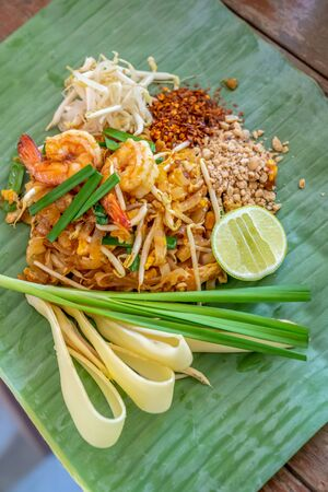PadThai, The Traditional of Thailand Fried noodle with prawns on the banana leaf ready to serve for lunch.