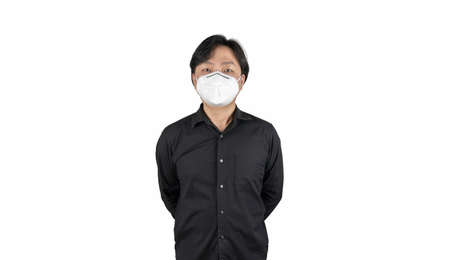 Asian middle man in a black shirt, wears a white n95 mask, stands in front of a white clear background. 免版税图像
