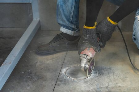 Construction worker is cutting the floor by medium blade machine to circle hold shape with a lot of dust around it for install closet with.