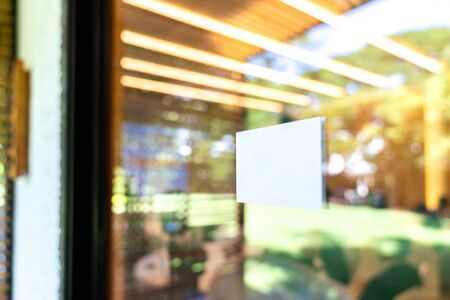White rectangle are sticked on the glass door in front of seminar hall with blur bokeh background. Imagens