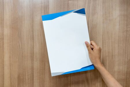 Asian person is holding and raising up the empty a4 paper on the wood background.