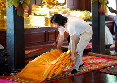 Asian Man supports and prepares orange monk seat on the red carpet in wood pavilion temple.