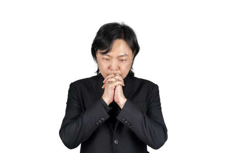 Isolated Asian business man in black suit hand together and prays for something on white background. Clipping Path.