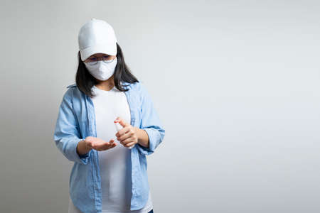 Asian young female in a casual blue t-shirt and white cap is spraying and washing her hand by a small alcohol spray bottle on her hand. white clear background studio light. 免版税图像