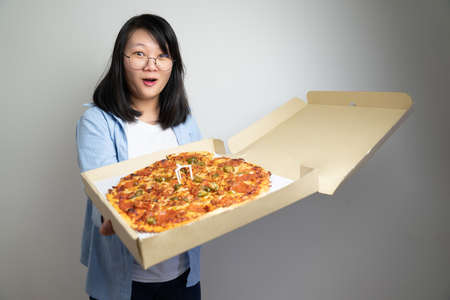Asian glasses young woman opens Pizza Box and excites about the large size pizza in it. Shooting in studio light. 免版税图像