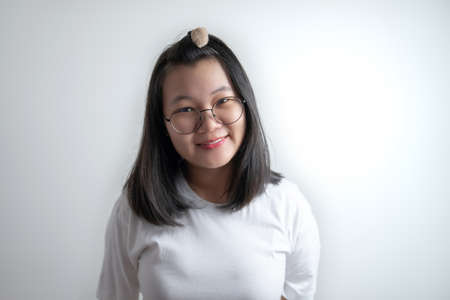 portrait of Asian young pretty girl with her eyes glasses and white casual t-shirt in studio light clear white background.