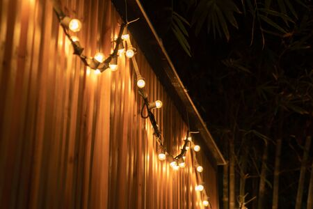 tungsten ball lamp light in the line are hanged on to wood battens partition at outdoor night with bamboo tree background. Stockfoto