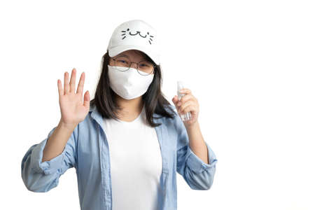 Asian young female in a casual blue t-shirt and white cap is spraying and washing her hand by a small alcohol spray bottle on her hand. white clear background studio light. Stockfoto