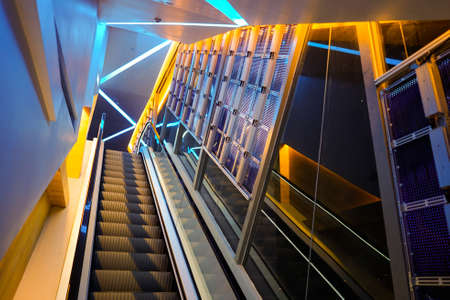 escalator with LED light beside in technology abstract neon colorful light theme. Redactioneel