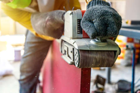 Carpenter is shaving red wood door by his shaving machine in outdoor field with steel pole building structure environment.
