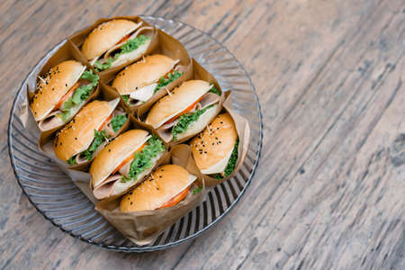 A group of homemade HAMBURGER is wrapped with paper craft and arranged on the dish, ready to serve and eat.