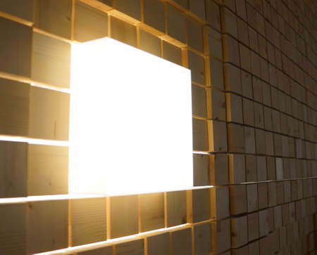 Acrylic square light box on the square wood cube are decorated on the wall in the dark room.