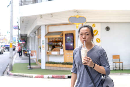 Asian man holds the bubble ball ice Milk Tea in front of the shop on the outdoor street footpath.