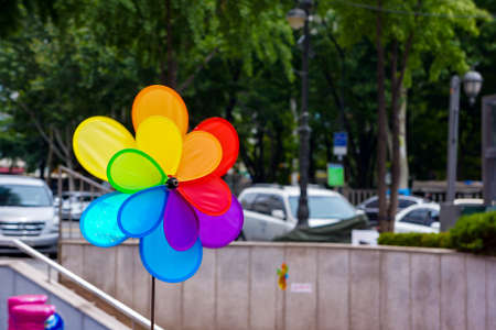 Colourful Wind turbine in the city on the road and a lot of car are driven on it. 免版税图像